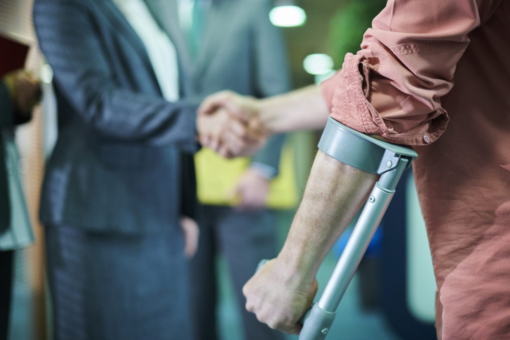 man with crutches shaking hands with workers compensation attorney